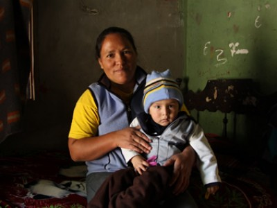 mother holding child inside home