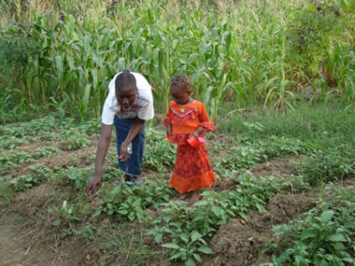 a man and child farming plants