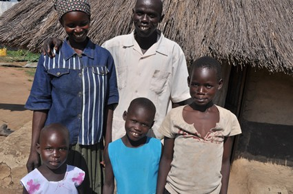 Man woman and three children standing outside a grass hut.