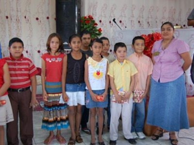 woman with group of children holding gifts