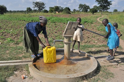 Woman filling a water container with the help of children.