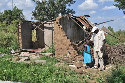 Man and small child standing outside a destroyed house.