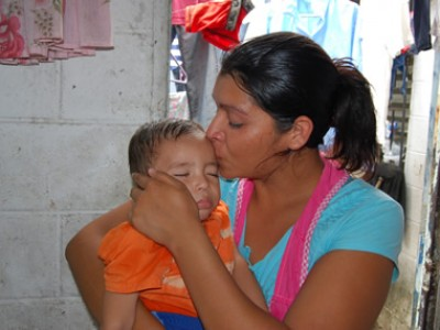 A woman kissing a baby on the forehead