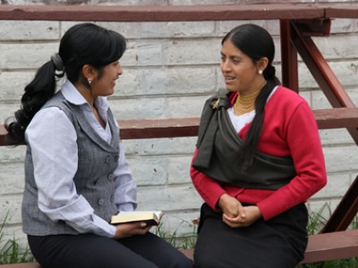 two women sitting on bench talking to each other
