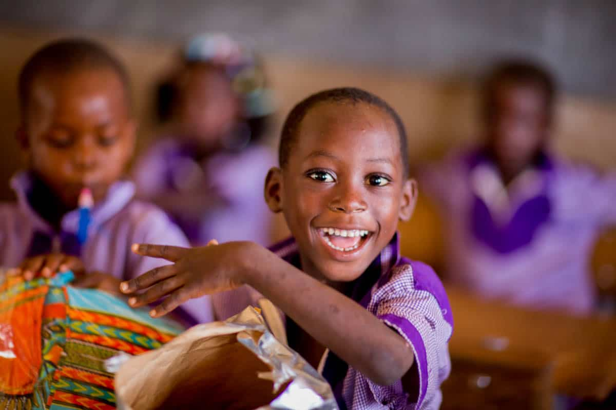 What Does the Bible Say About Giving? A boy in a purple school uniform opens a brightly wrapped present.