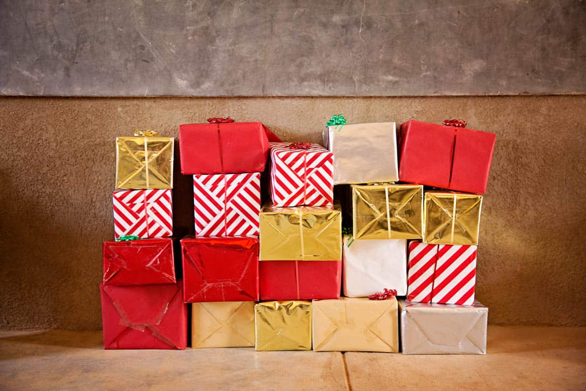 What Does the Bible Say About Giving? A stack of brightly colored presents sits against a wall