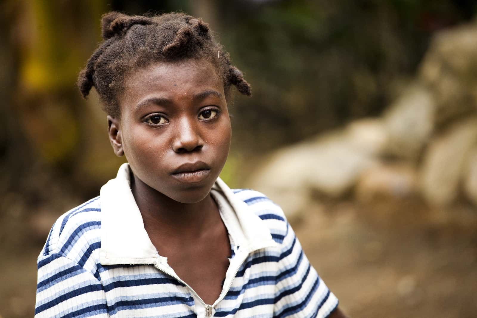 Brokenness Before God: A teenage girl sits, with a solemn look on her face, wearing a white and black striped shirt