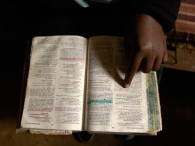 hand pointing to word in open Bible