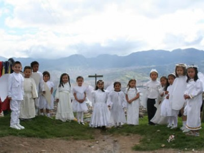 Children standing outside by a cross.