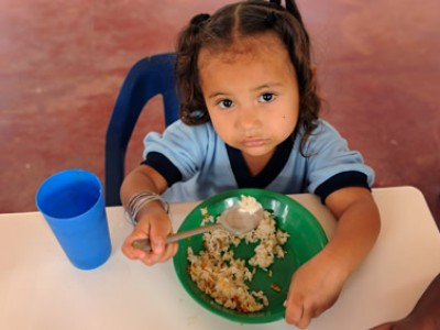 little girl sitting at a table eating rice and beans from a green plate with a blue cup beside her