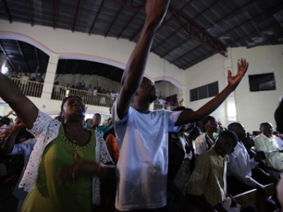 people in church worshiping with arms raised