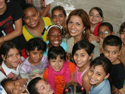 young woman surrounded by group of children