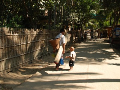 child walking with a man carrying mat
