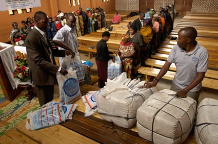 people in line to receive food baskets in a church