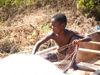 Young boy in a boat with a fishing net.