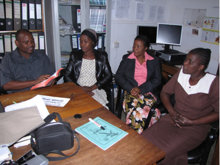 Three ladies and a man sitting in an office.