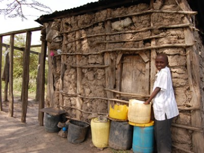girl standing outside of home made of mud
