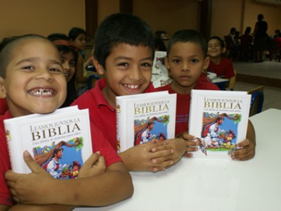 three smiling boys in red shirts holding a bible with their arms resting on a table