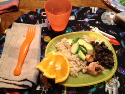 Meal on a green plate with an orange cup and orange fork