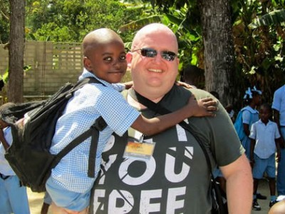 Man with sunglasses holding on to a child in a blue shirt with a black backpack