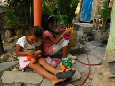 girls sitting outside playing with dolls