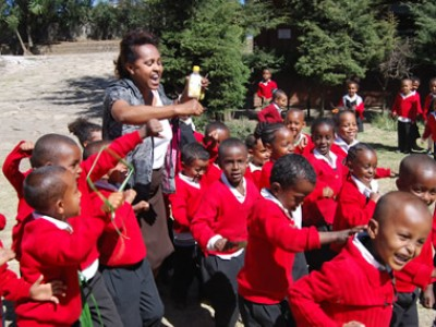 group of children wearing red sweaters outside with an adult