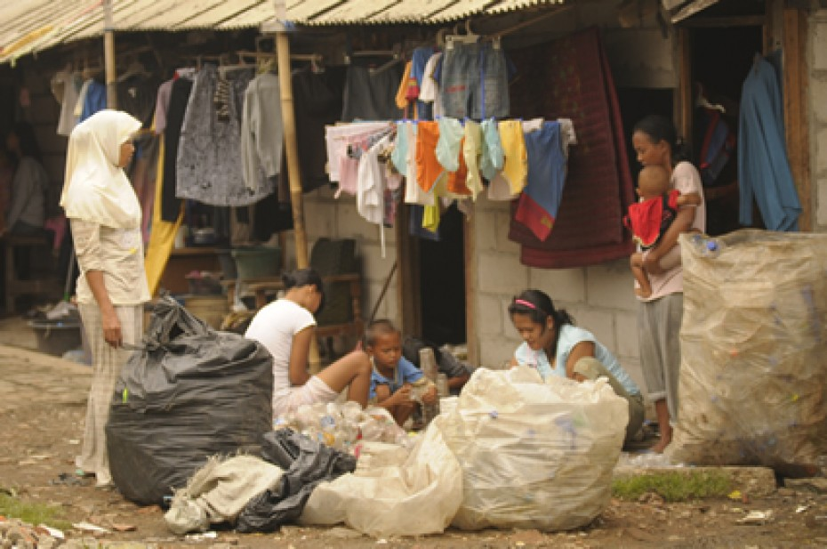 people outside house surrounded by filled garbage bags