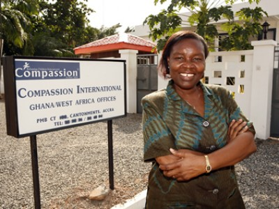 Jemima Amanor standing in front of Compassion sign