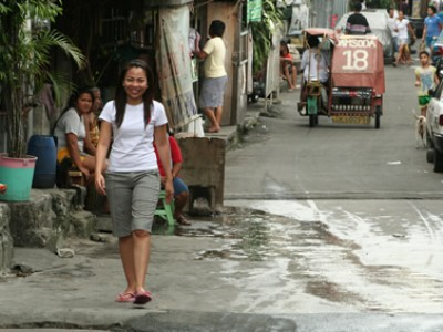 a smiling girl in a white shirt and gray shorts walking down a street