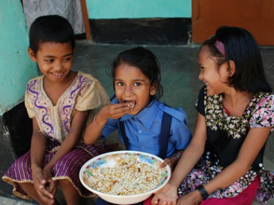 Three children eating rice from a large bowl