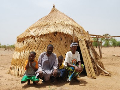 Family outside of a grass hut.