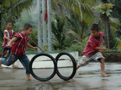 children rolling tires in a race