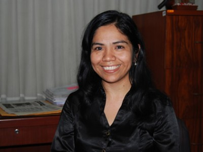 a youg smiling woman in a black blouse in an office