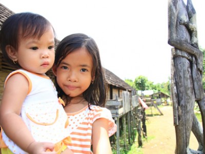 Two young children standing next to a wooden hut.