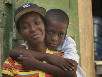 a boy with his arms wrapped around his mother who is wearing a black baseball cap