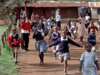 school children running down road in Kenya