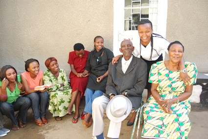 group of smiling women honoring an elderly couple