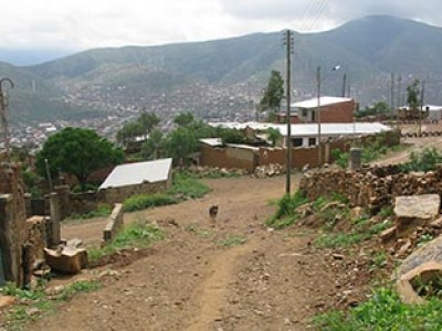 dirt road on hillside with a few buildings