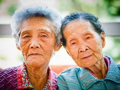 two elderly women with their heads together