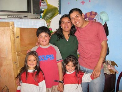 man and woman posing with three children
