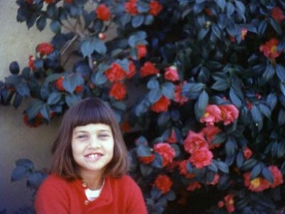 young smiling girl next to a large bush