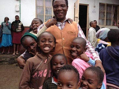 man embracing group of children