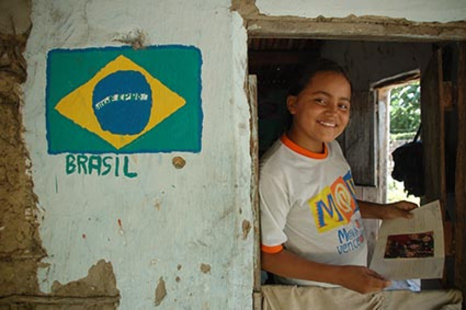 A child leans against a wall with a Brazilian flag on it