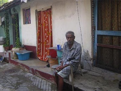 older man sitting outside home in India