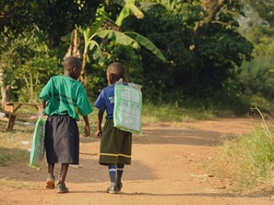 Two children walking on a dirt path.