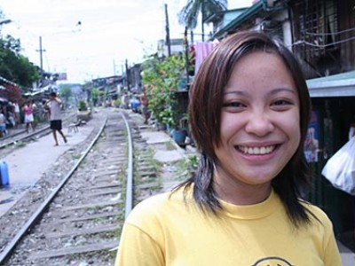 smiling young lady near railroad tracks