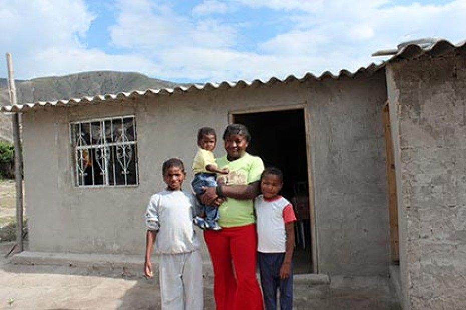 woman with children standing outside house