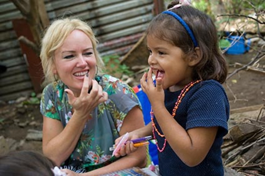 A women in a blue flowered blouse sitting next to a little girl wearing a blue shirt both touching their mouths with their hands