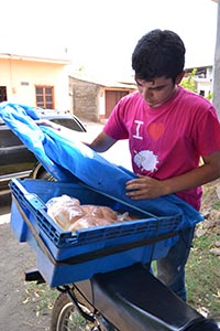 young man placing baked goods in container on back of motorbike