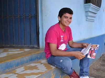 boy in a red shirt and denim pants sitting on a step holding a piece of paper
